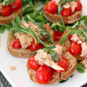 Tuna Toast topped with cherry tomatoes and arugula