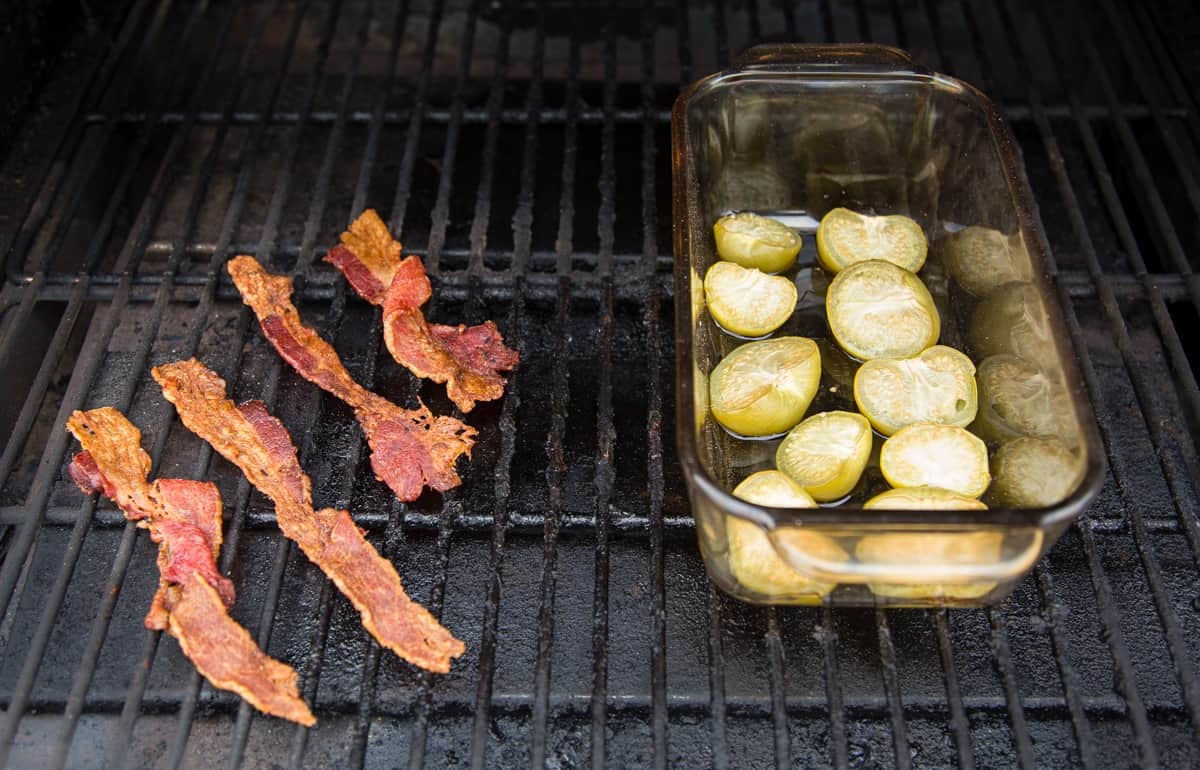 A bowl of tomatillos and 4 pieces of bacon cooking on a smoker