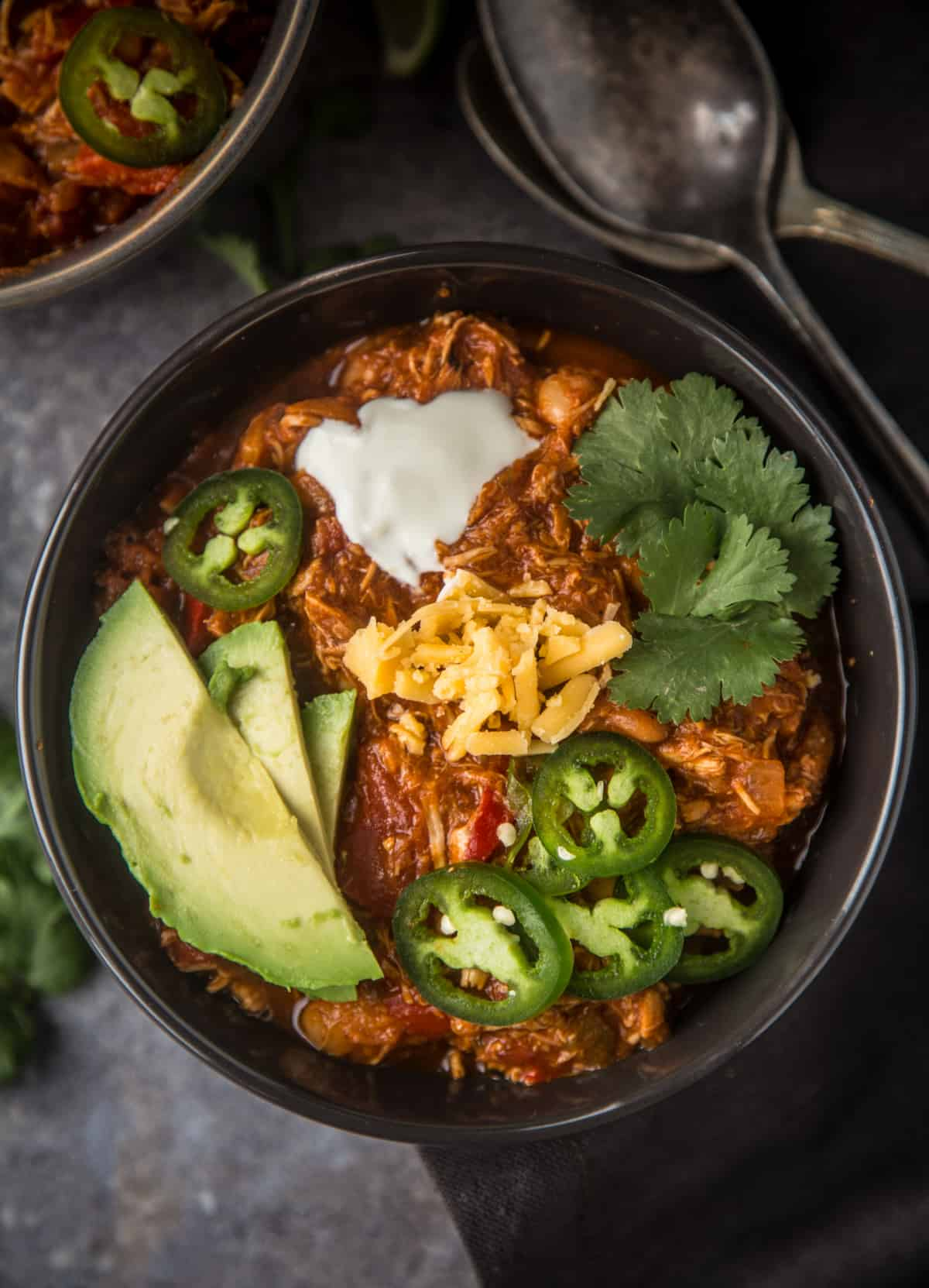 A bowl of easy smoked chicken chili topped with avocado, cheese, and jalapeño