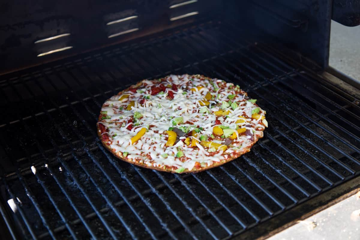 A frozen pizza cooking on a pellet grill