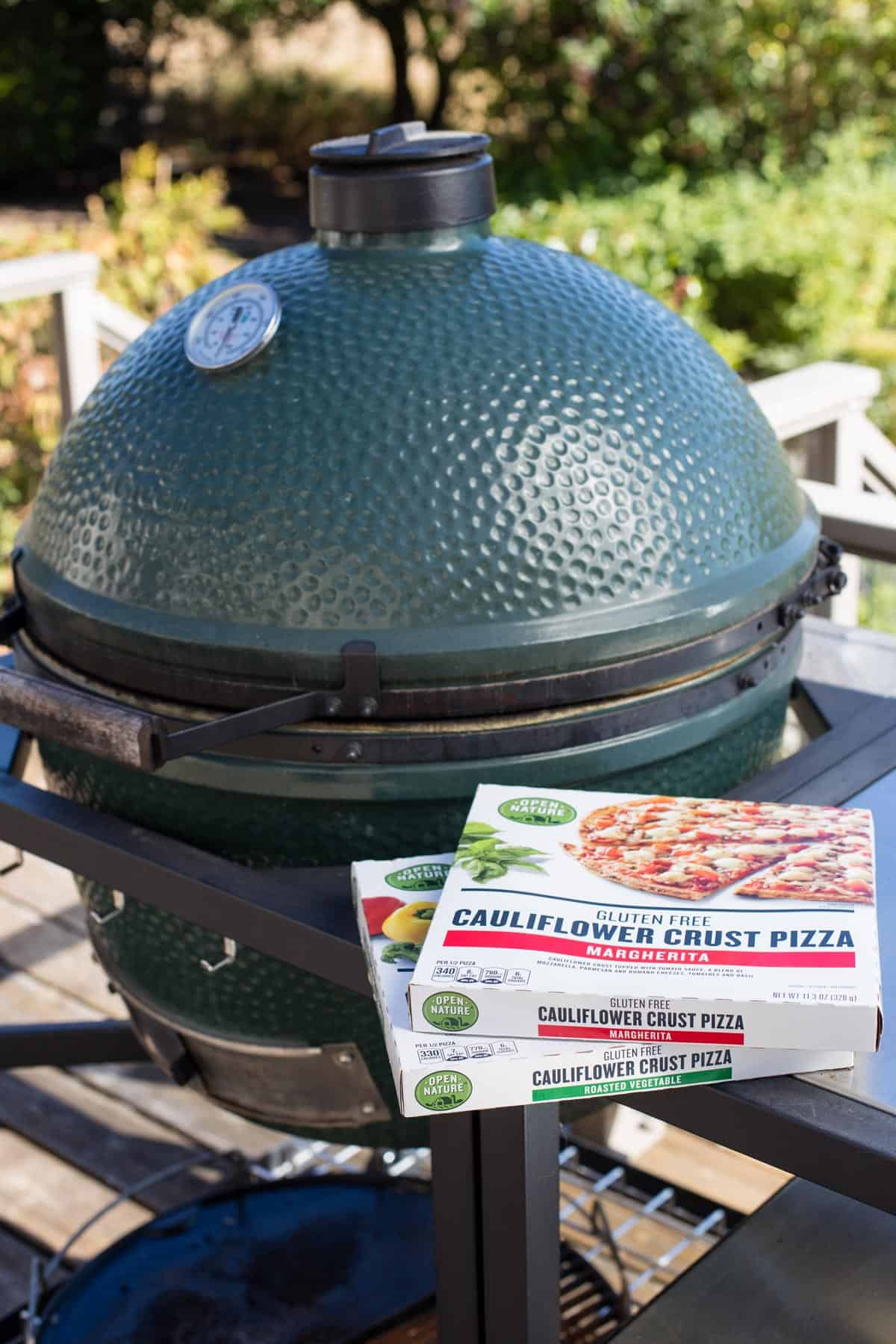 Two frozen pizzas right next to a Big Green Egg grill