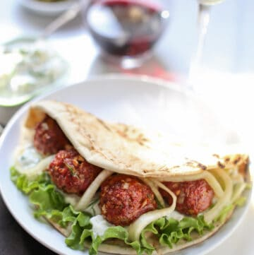 Smoked Lamb Meatball Pita on a plate with a glass of wine