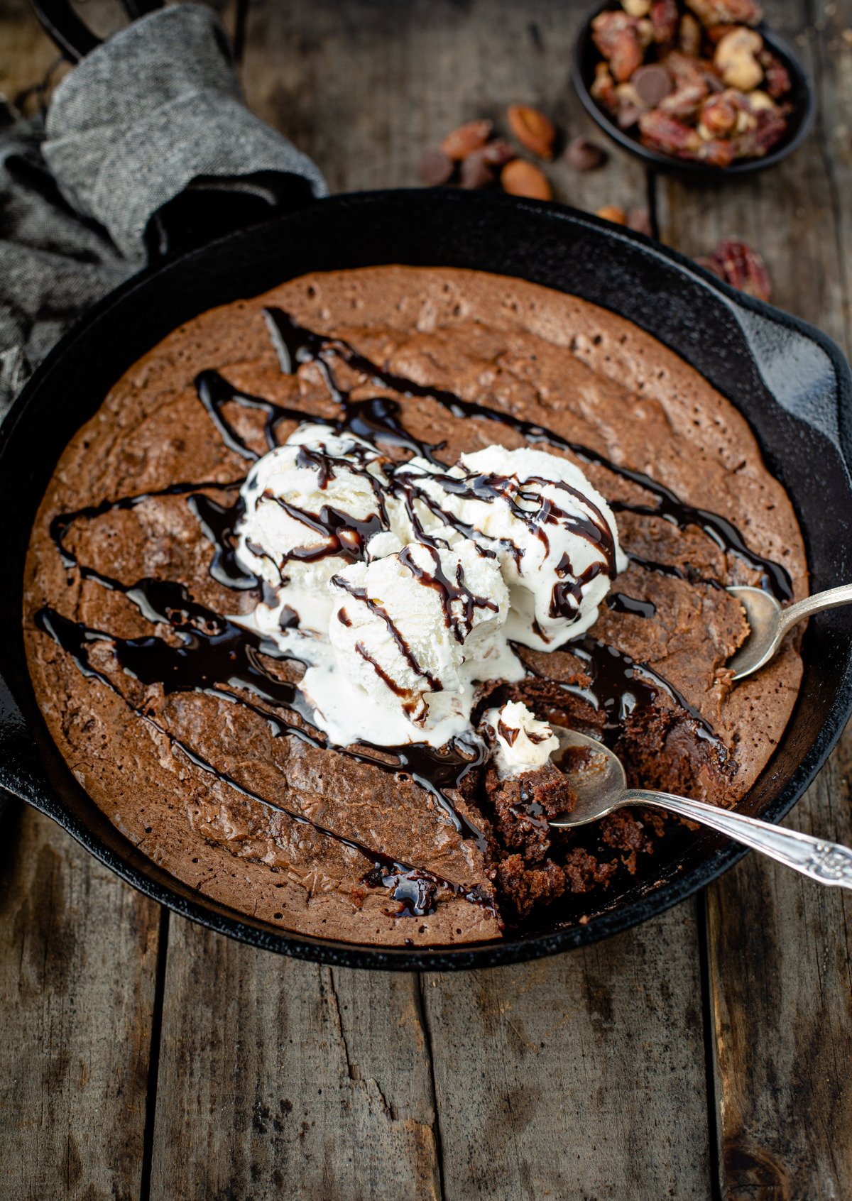 Skillet brownies with ice cream and a chocolate sauce drizzle for dessert comfort food.