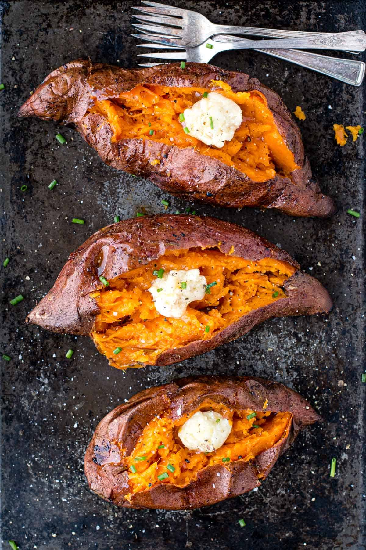 Three Grilled Sweet Potatoes on a sheet pan topped with smoked honey butter