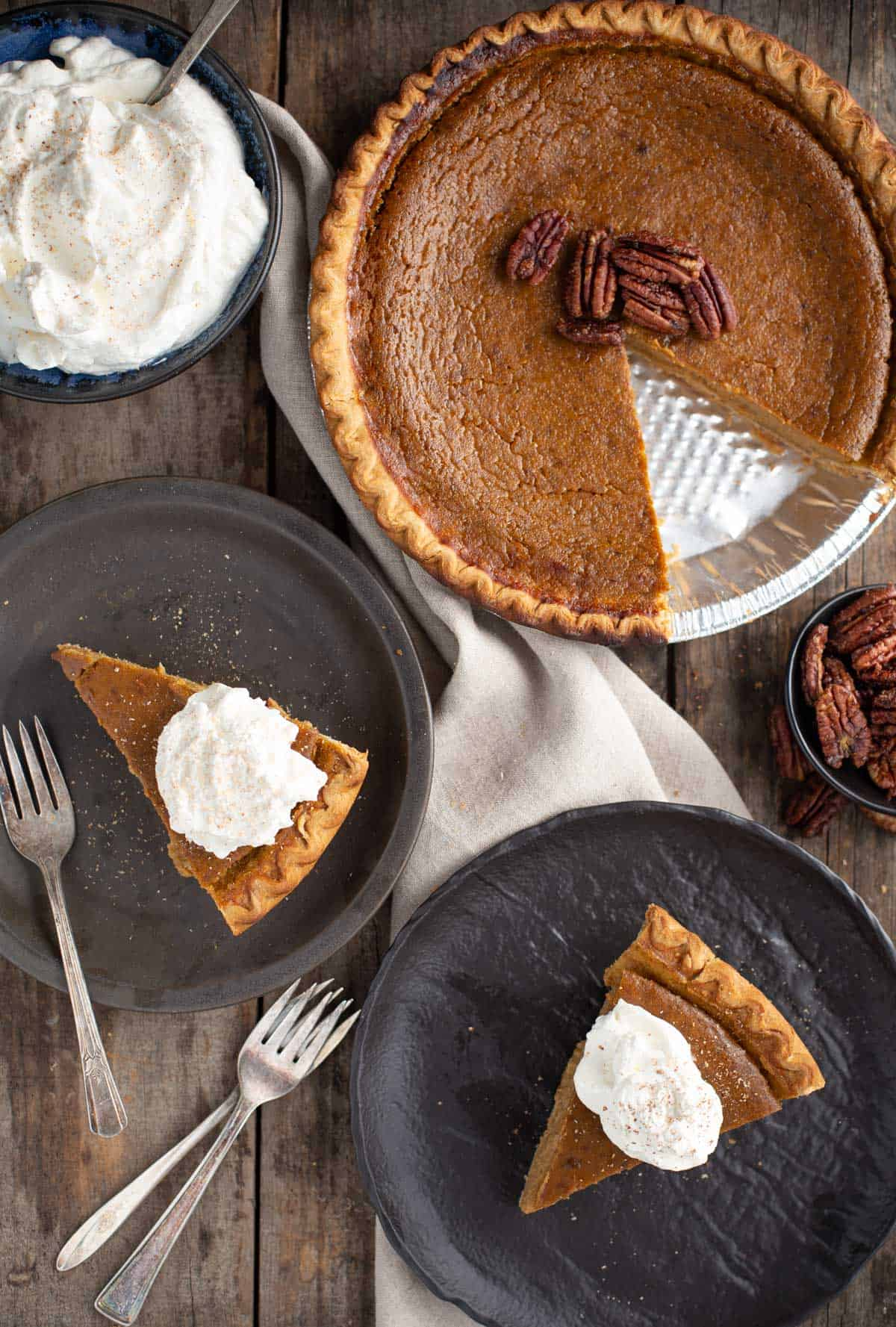 A grilled Pumpkin Pie with candied pecans and two slices on a plates