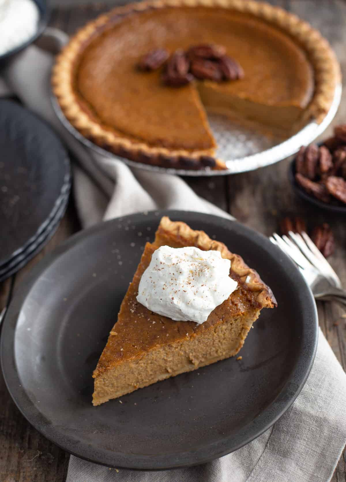 A slice of grilled pumpkin pie on a black plate