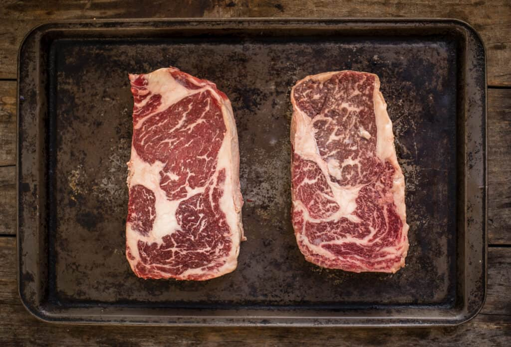 Prime marbled ribeye on the left and American Wagyu on the right and unseasoned.