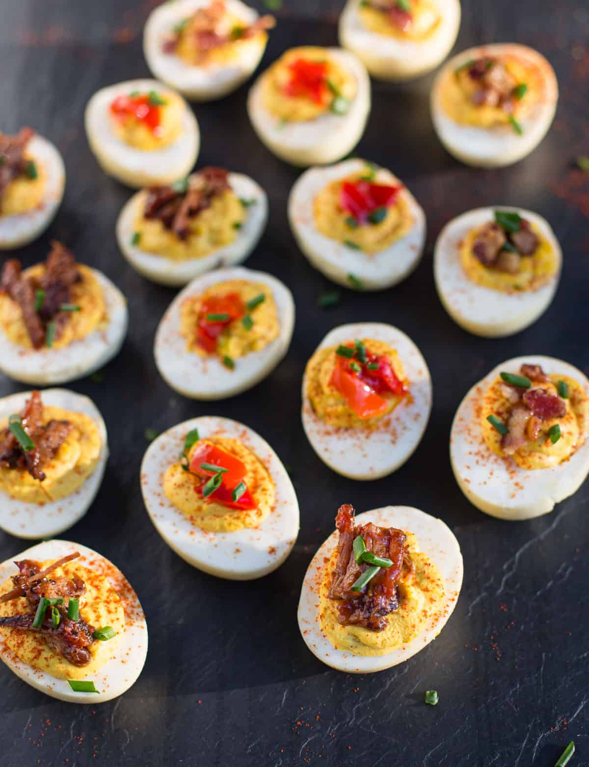Deviled Eggs topped with brisket and Mama Lil's peppers on a slate platter