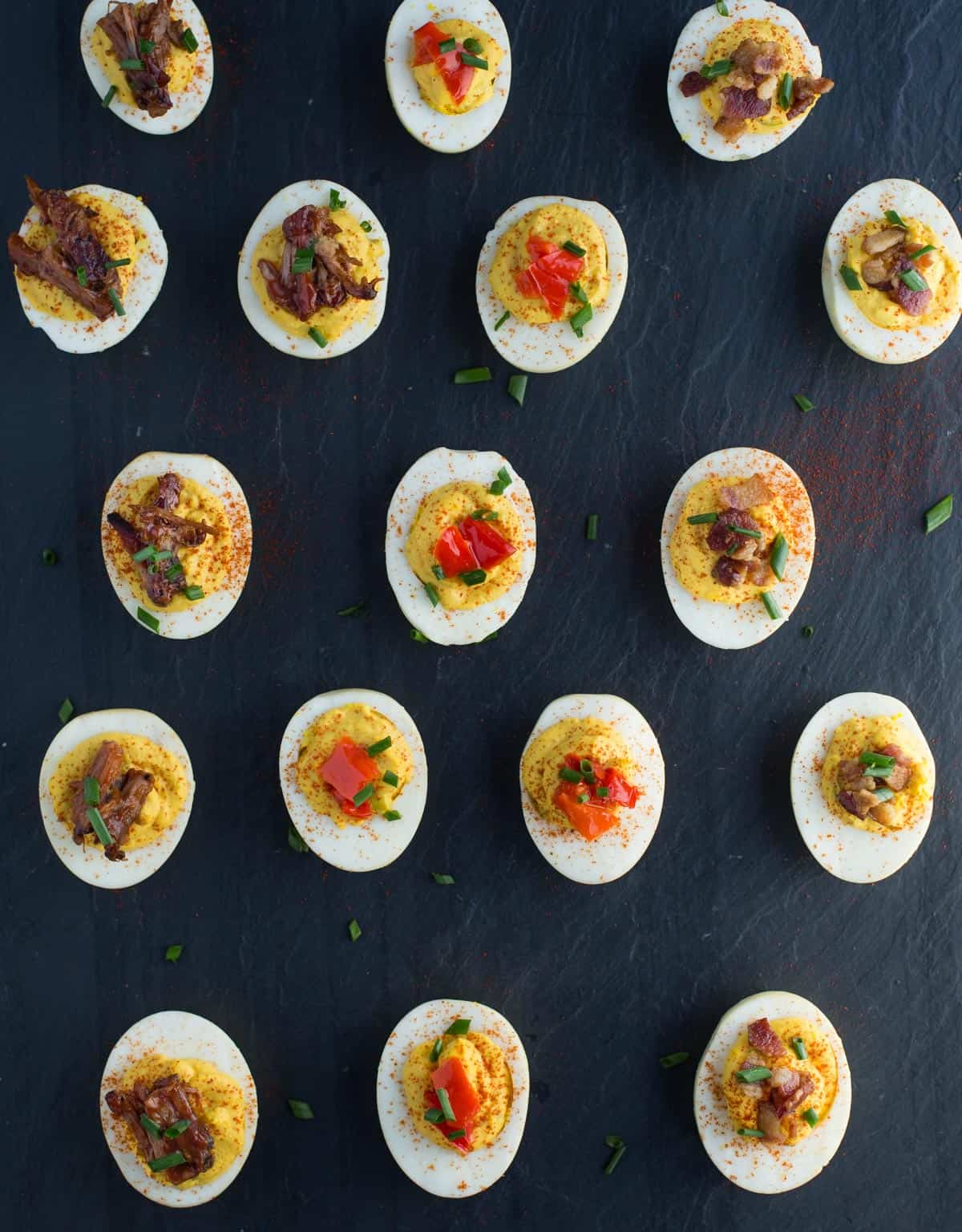 A platter full of smoked deviled eggs topped with brisket, pickled peppers, and crispy bacon