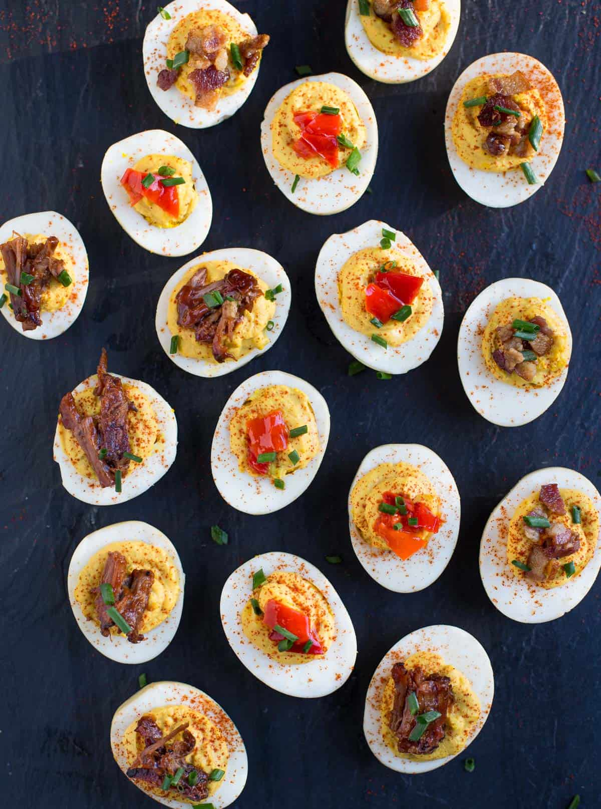 A platter full of smoked deviled eggs with mixed toppings