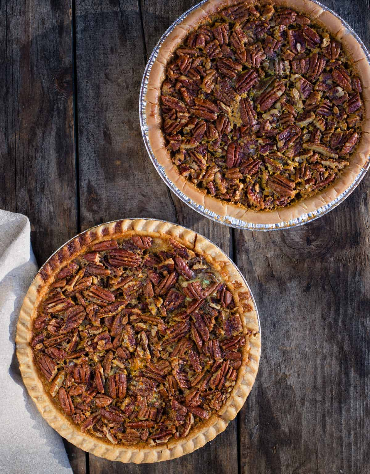 Two pecan pies resting on a wood board