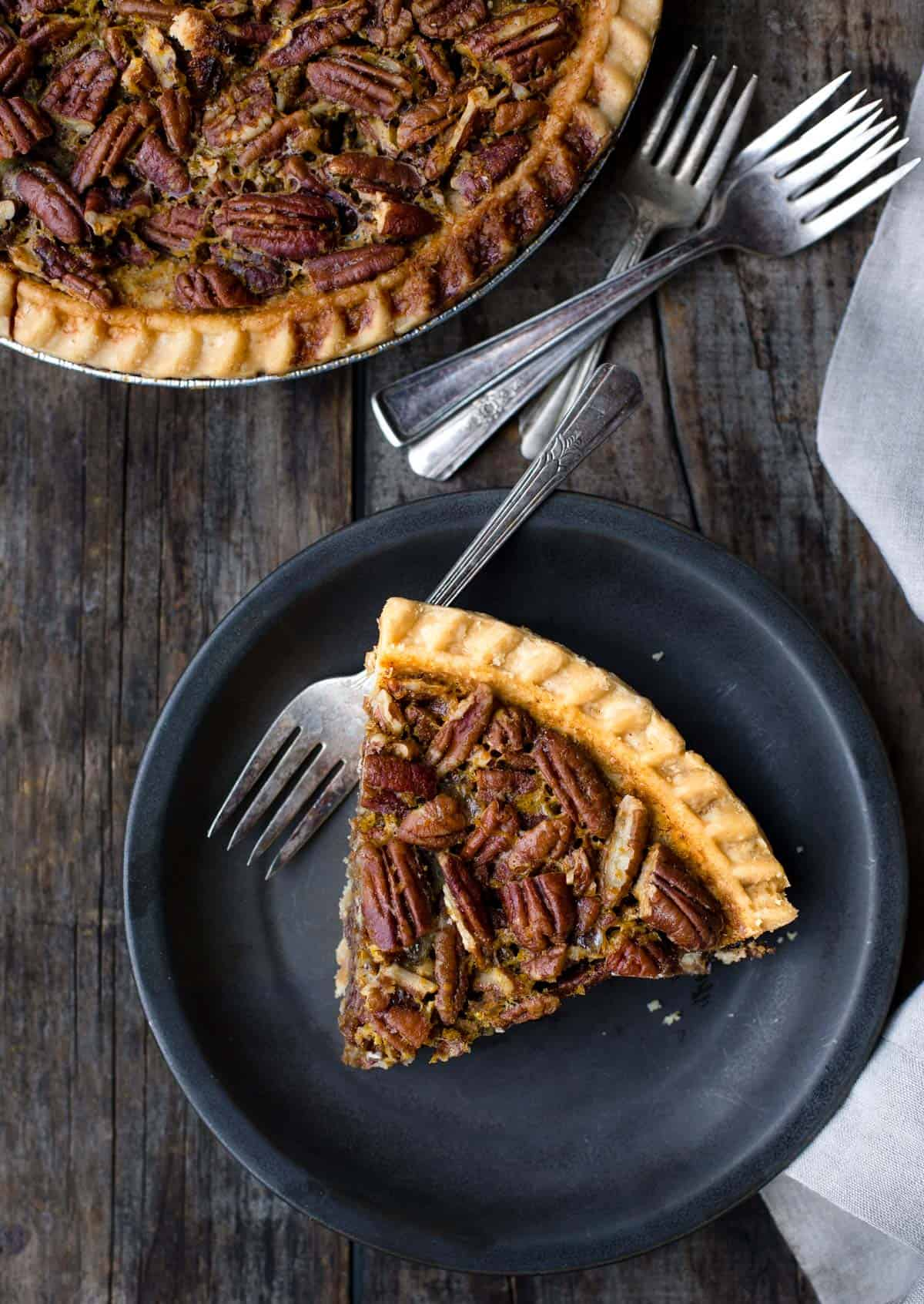 A slice of grilled pecan pie on a black plate