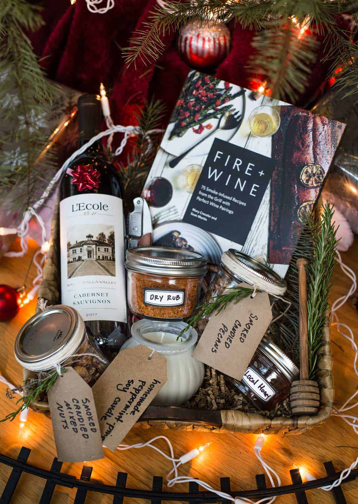 A holiday gift basket filled with edible gifts including L'Ecole wine, Fire + Wine cookbook, smoked mixed nuts, and other edible holiday gifts
