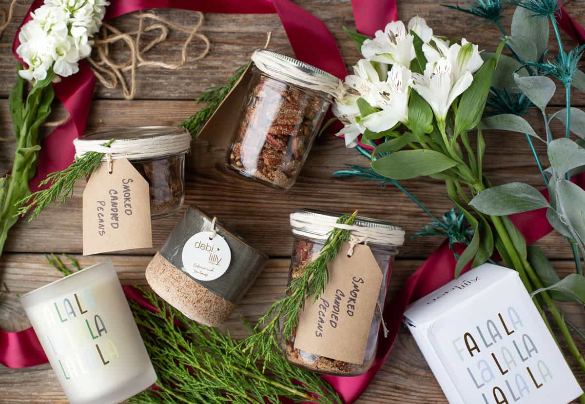 Jars of candied pecans, flowers, and candles, all arranged on a wood board as holiday gift ideas.