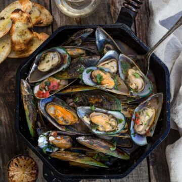 Grilled Mussels in a cast iron pan with broth and toasted bread.