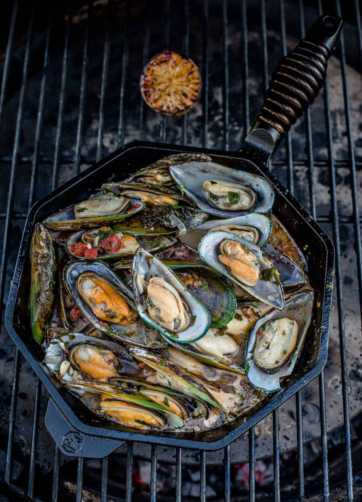 Grilled mussels in a cast iron pan on a hot grill