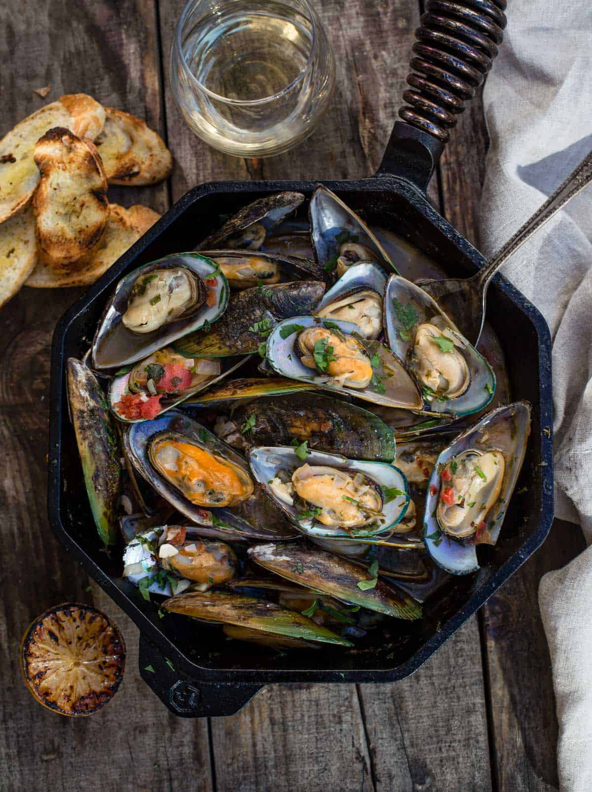Grilled mussels in a cast iron pan on a wood board with a glass of wine and a grilled lemon halves