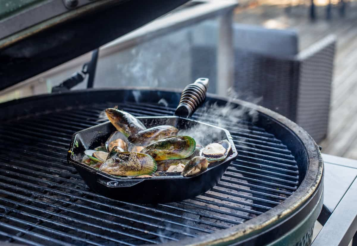 A cast iron pan filled with mussels on the hot grill
