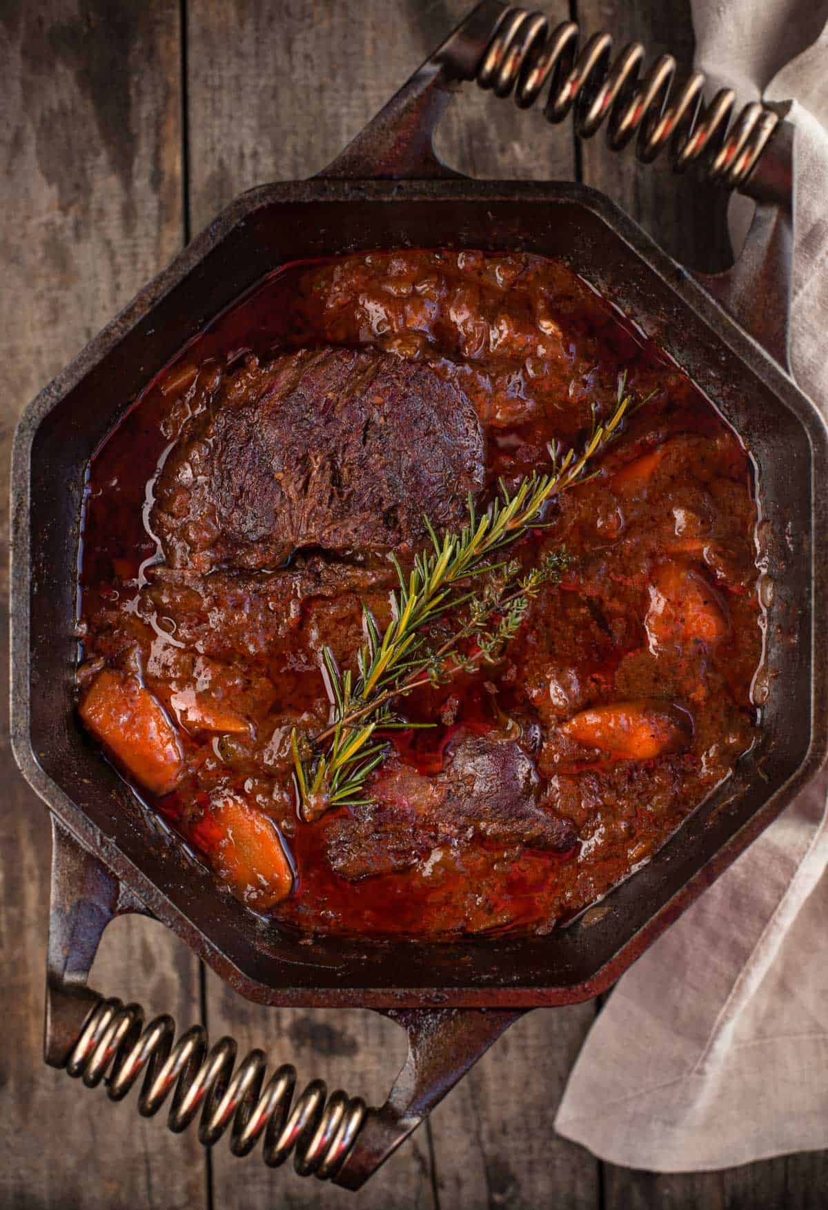 A smoked chuck roast pot roast stew in a large cast iron pan