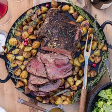 A smoked leg of lamb on a platter with roasted potatoes