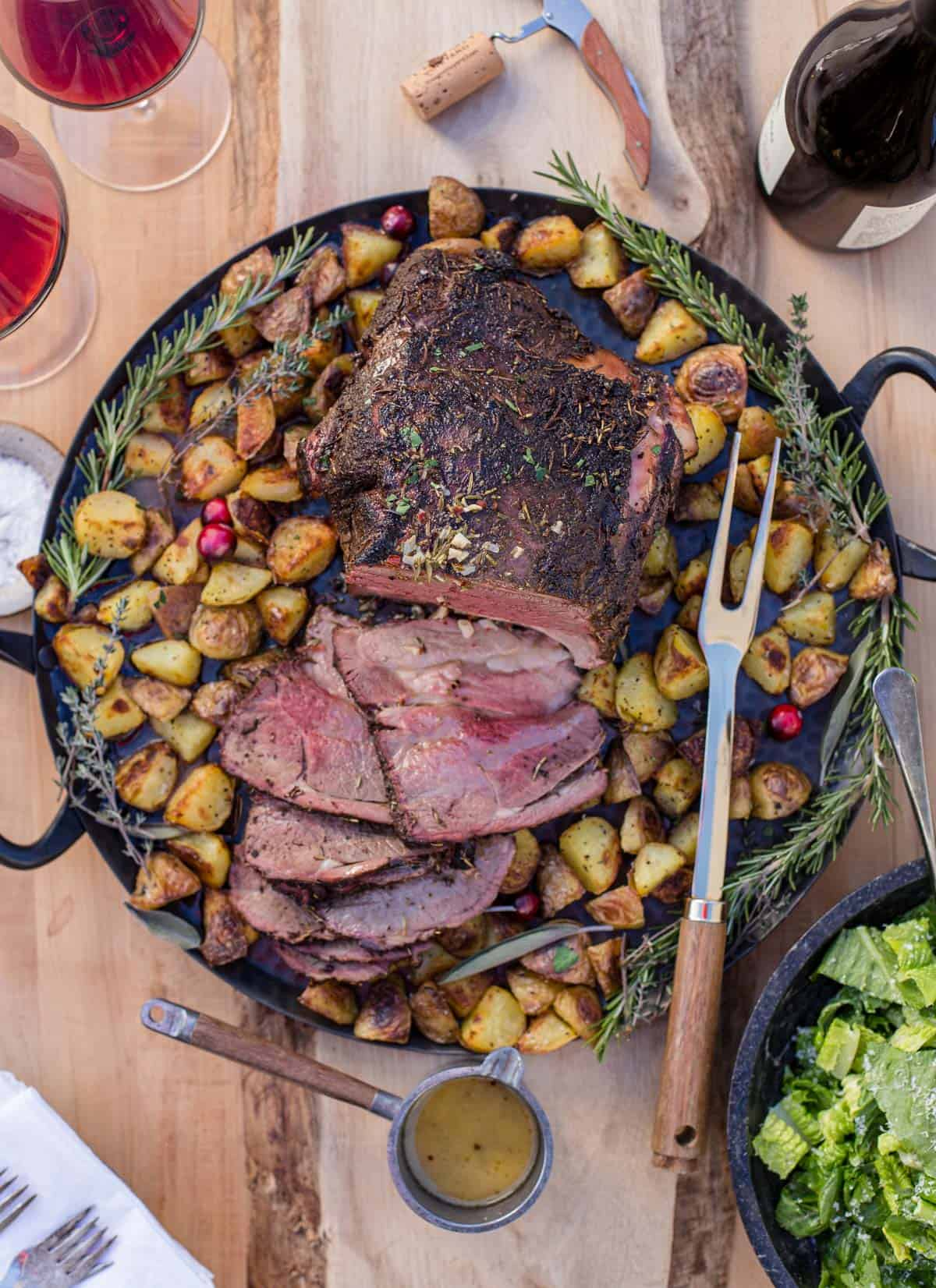 A bone in Smoked Leg of Lamb on a platter with roasted potatoes