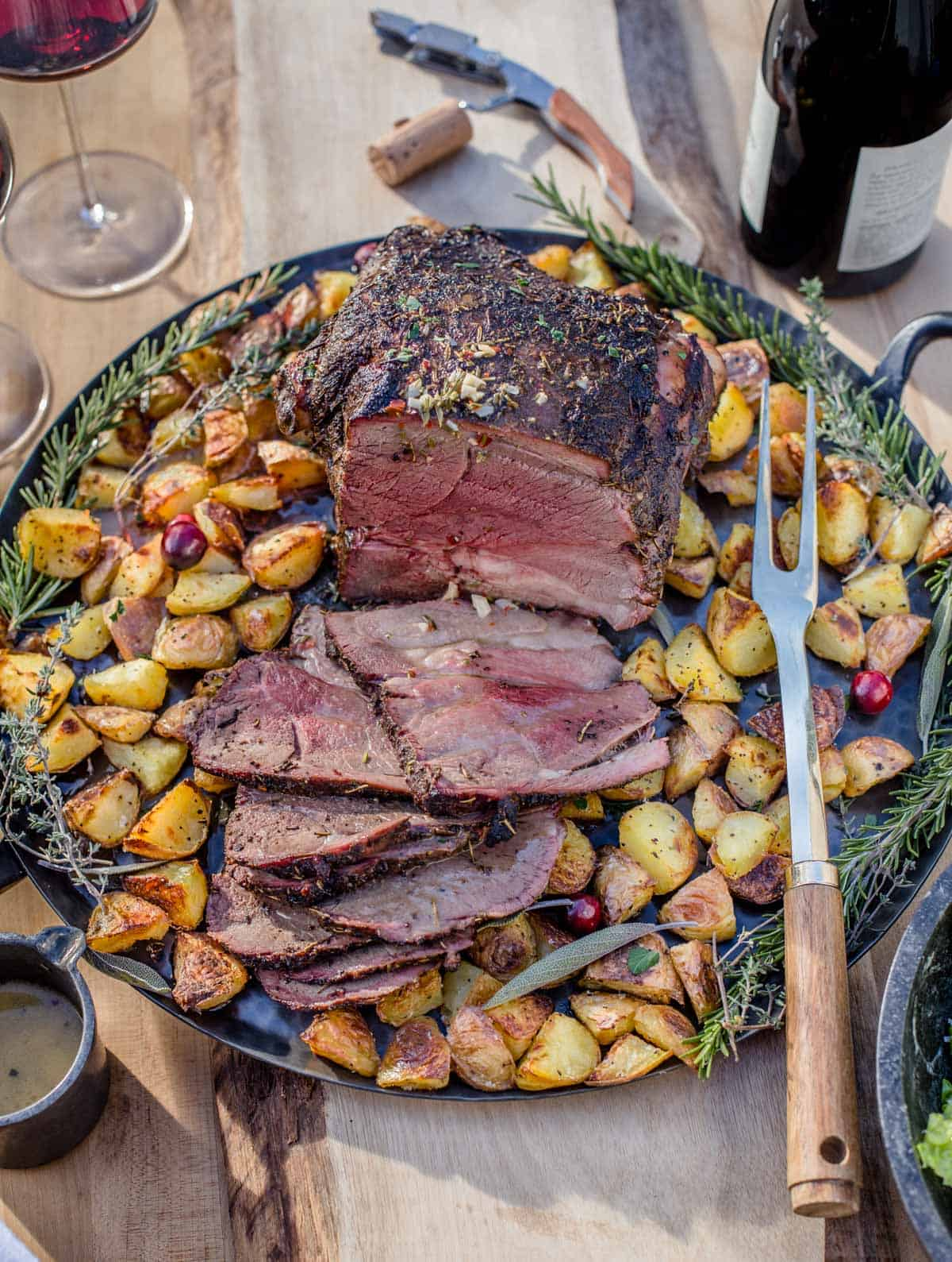 Slices of smoked leg of lamb on a platter with roasted potatoes