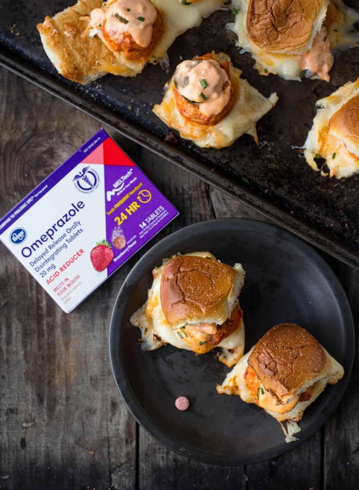 A platter of Buffalo Chicken Meatball Sliders alongside a package of Omeprazole