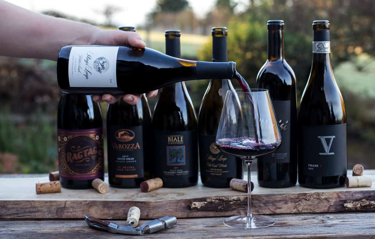 6 bottles of Petit Sirah wine in a lineup, with a bottle being poured into a glass