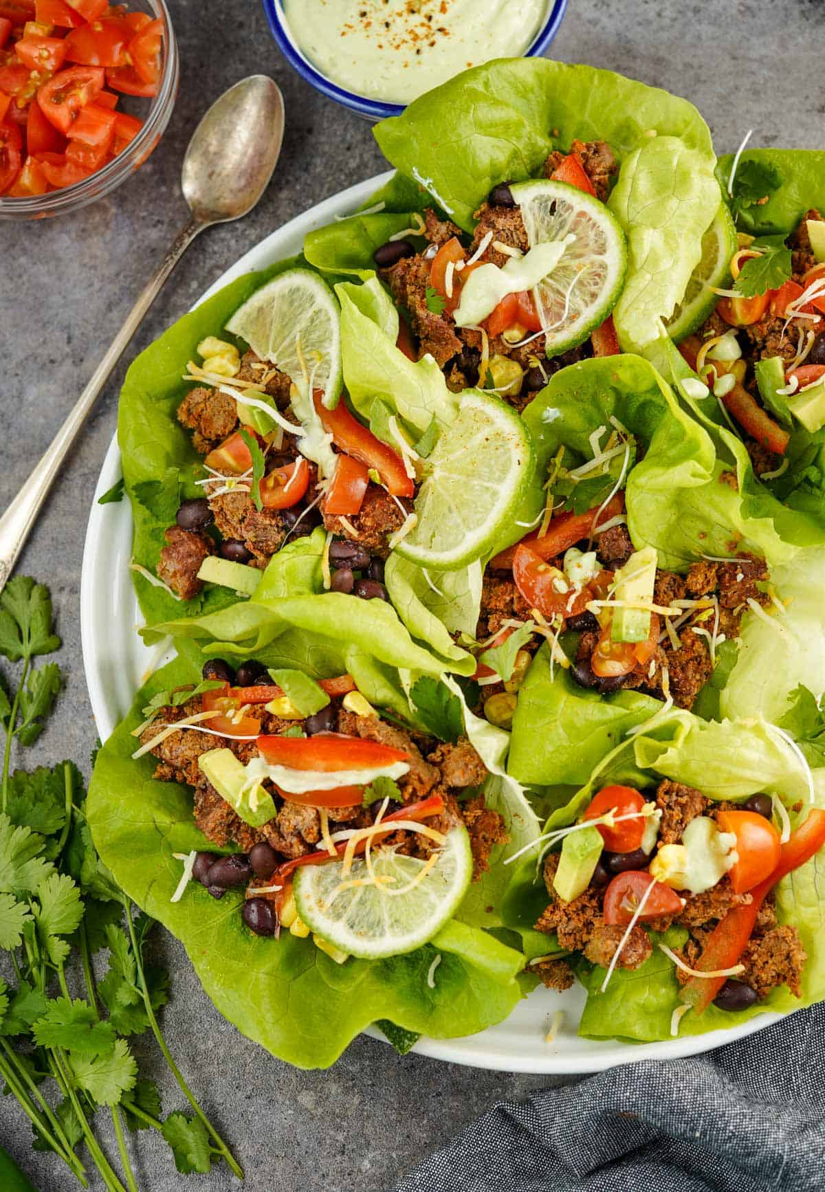 A plate full of Taco Lettuce Wraps filled with ground beef, diced tomatoes, limes, black beans, and avocado cream sauce
