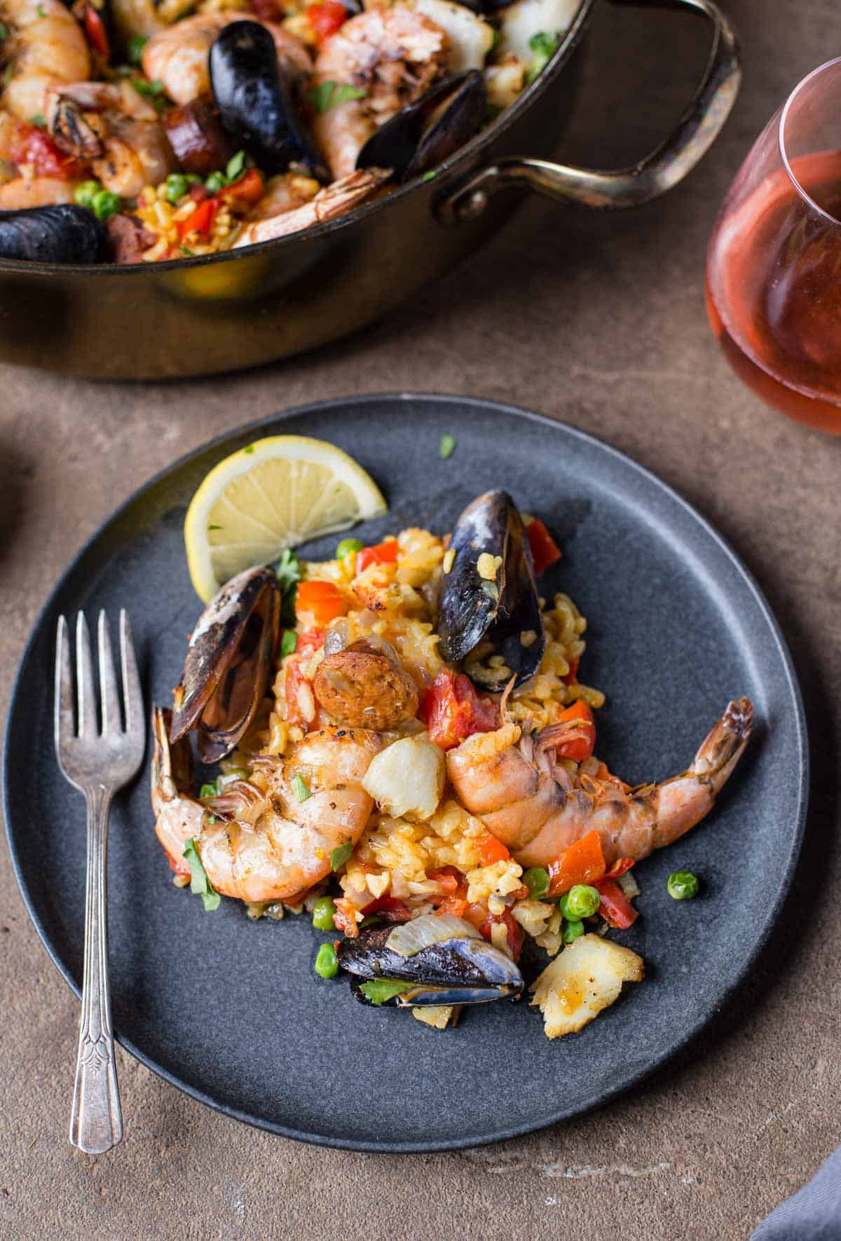 A grey plate with seafood paella and a glass of rosé wine next to it