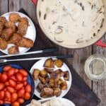 Cheese fondue platter with bread, tomatoes, and potatoes for dipping