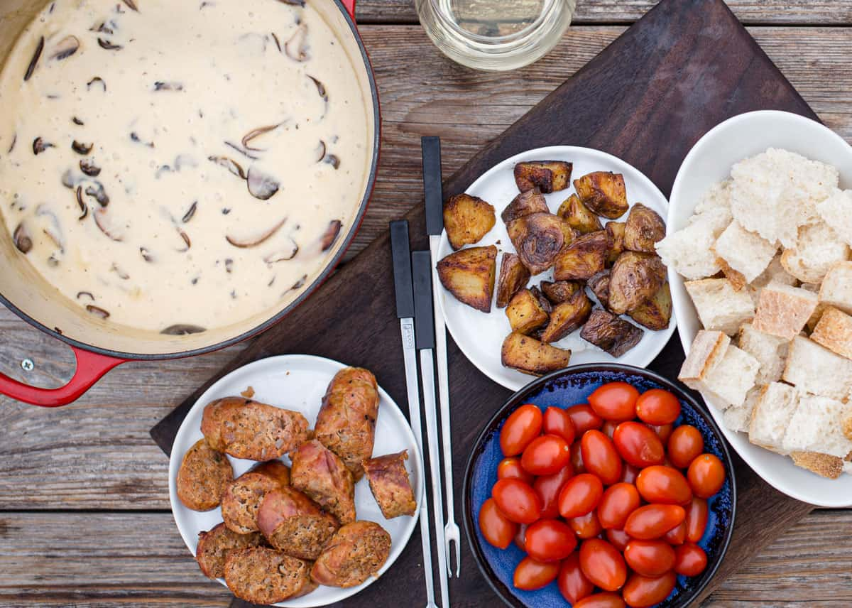 A platter filled with a pot of comté fondue and foods to dip into the cheese fondue