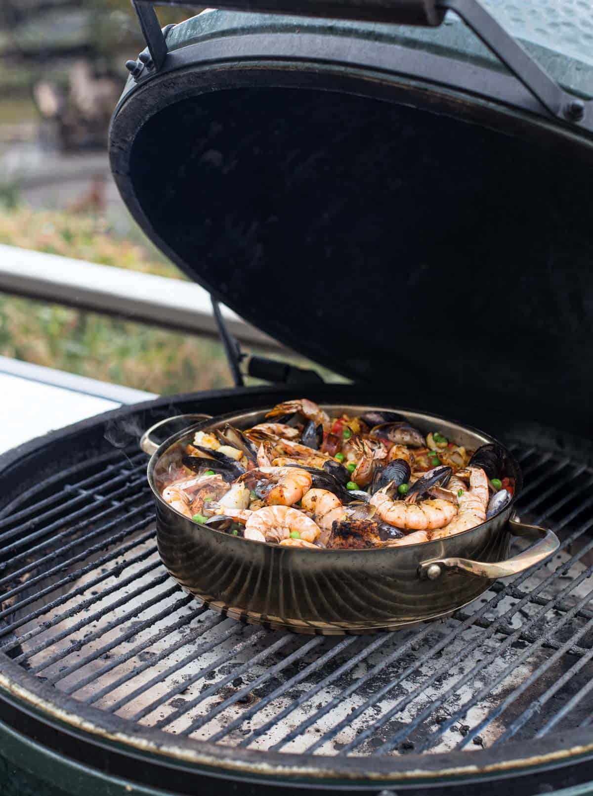 A pot of paella cooking on the grill