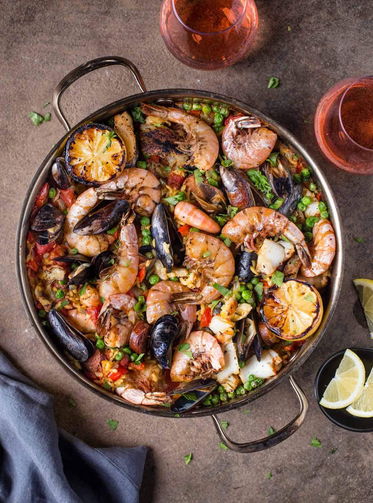 A pot of seafood paella with two glasses of rosé wine and a small bowl with lemon wedges