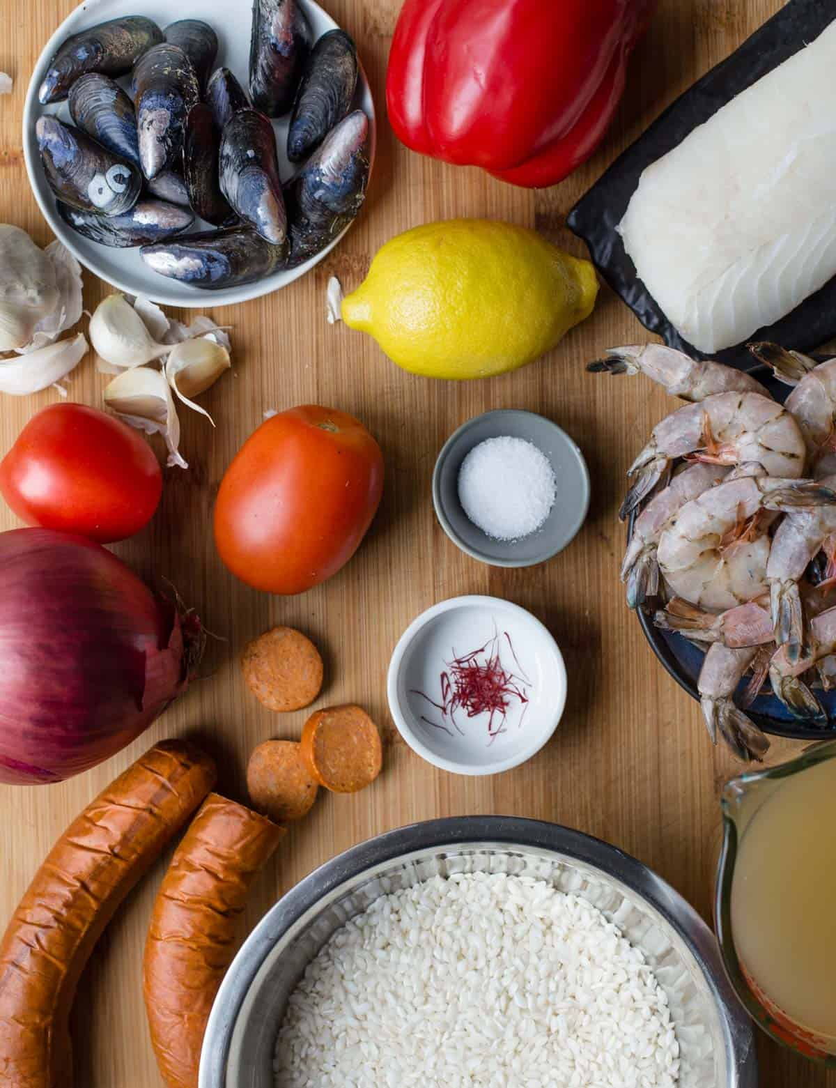 Ingredients for seafood paella on a wood cutting board