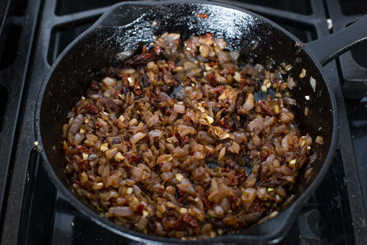 Caramelized onions, garlic, and sun dried tomatoes in a cast iron pan