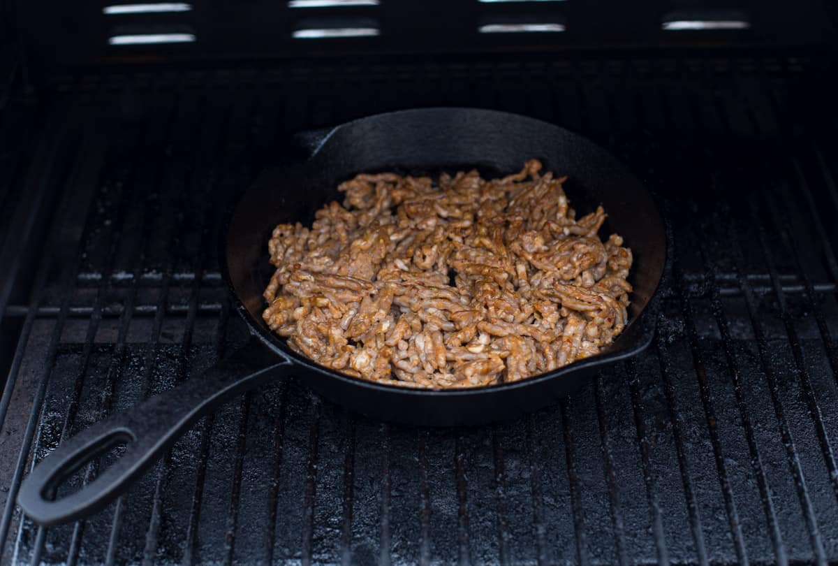 A cast iron pan with bulk sausage cooking inside a pellet smoker
