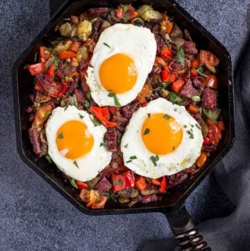 Corned beef hash in cast iron skillet with eggs sunnyside up.
