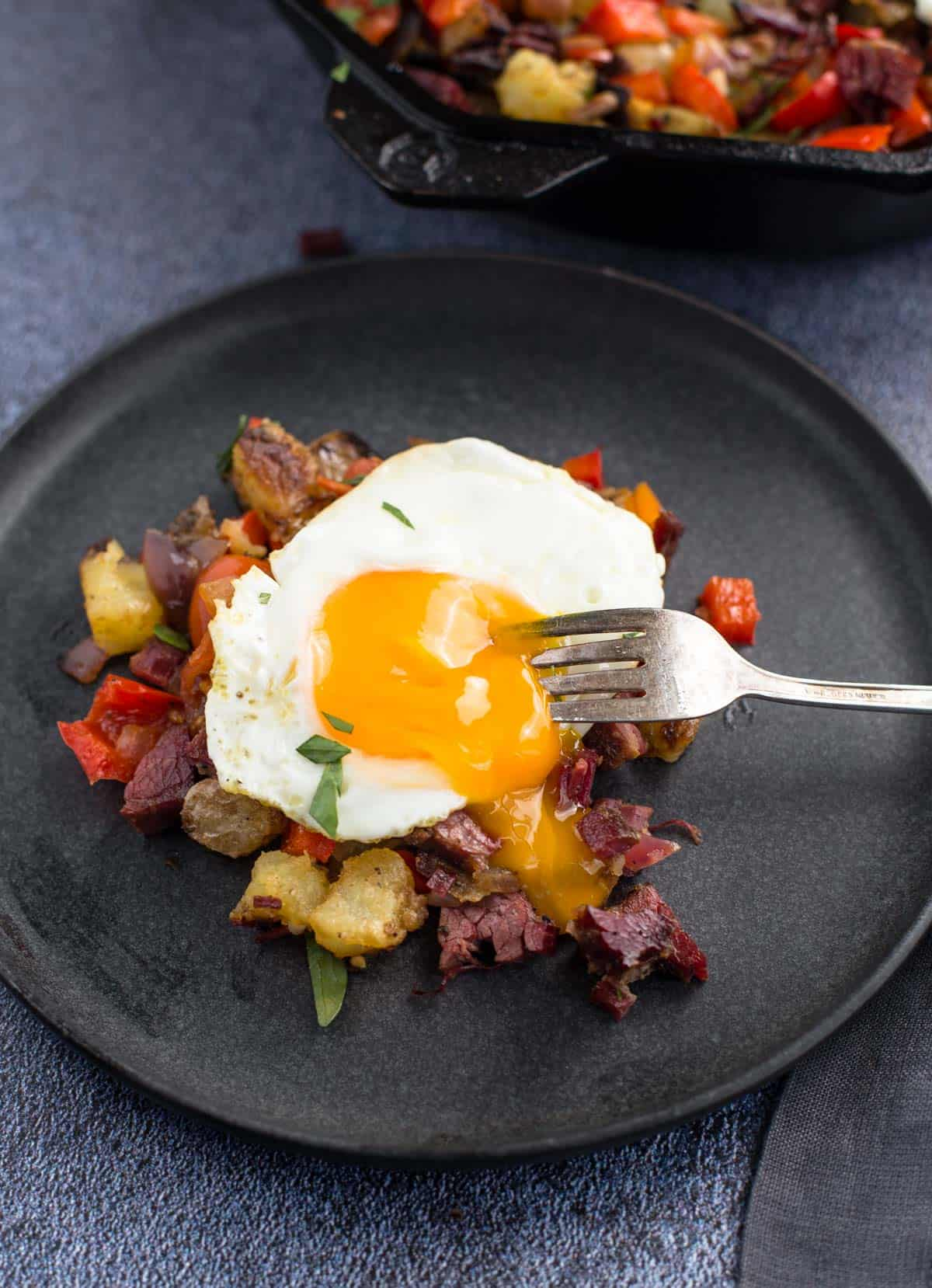 Egg sunny side up over corned beef hash on a small plate.