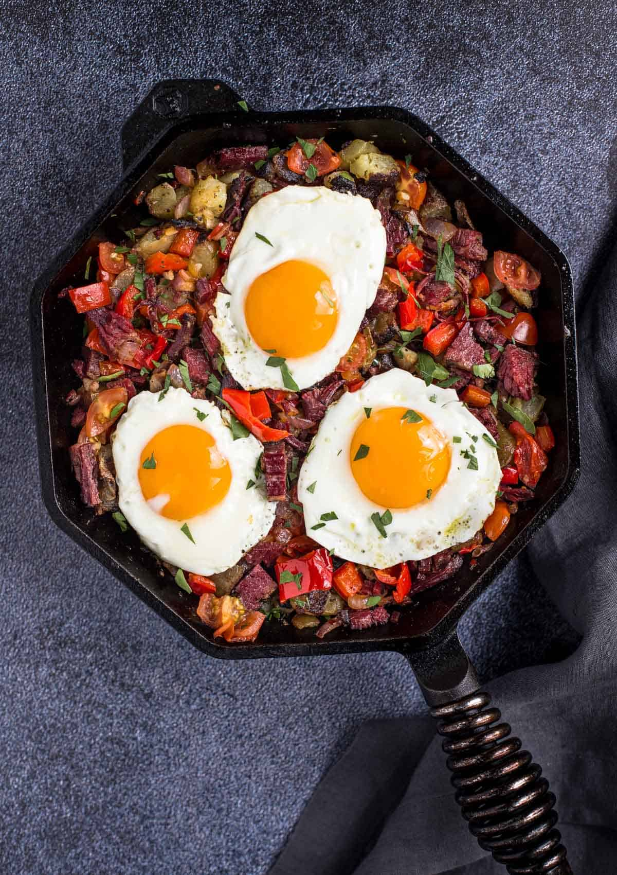 Skillet corned beef hash with eggs sunny side up.