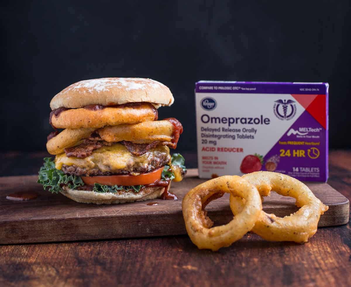 A Western Burger with Onion Rings on a wood board next to a box of Omeprazole