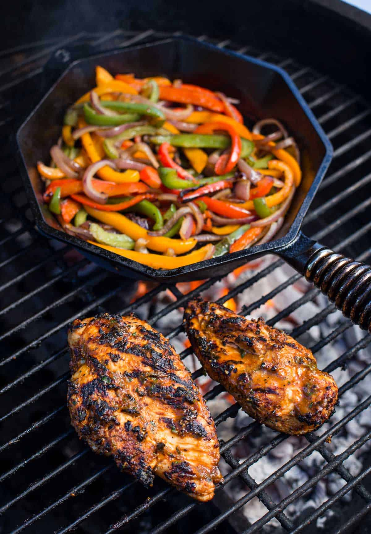 Chicken on the grill alongside peppers and onions cooking in a cast iron pan on the grill