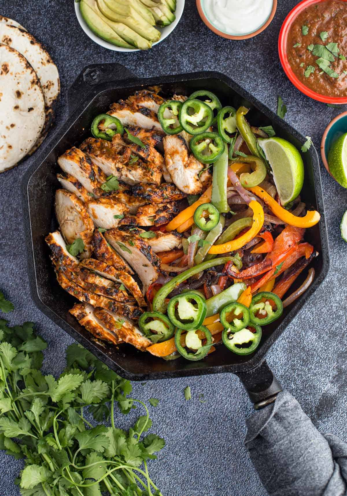Grilled Chicken Fajitas with vegetables in a cast iron pan surrounded by fajita toppings