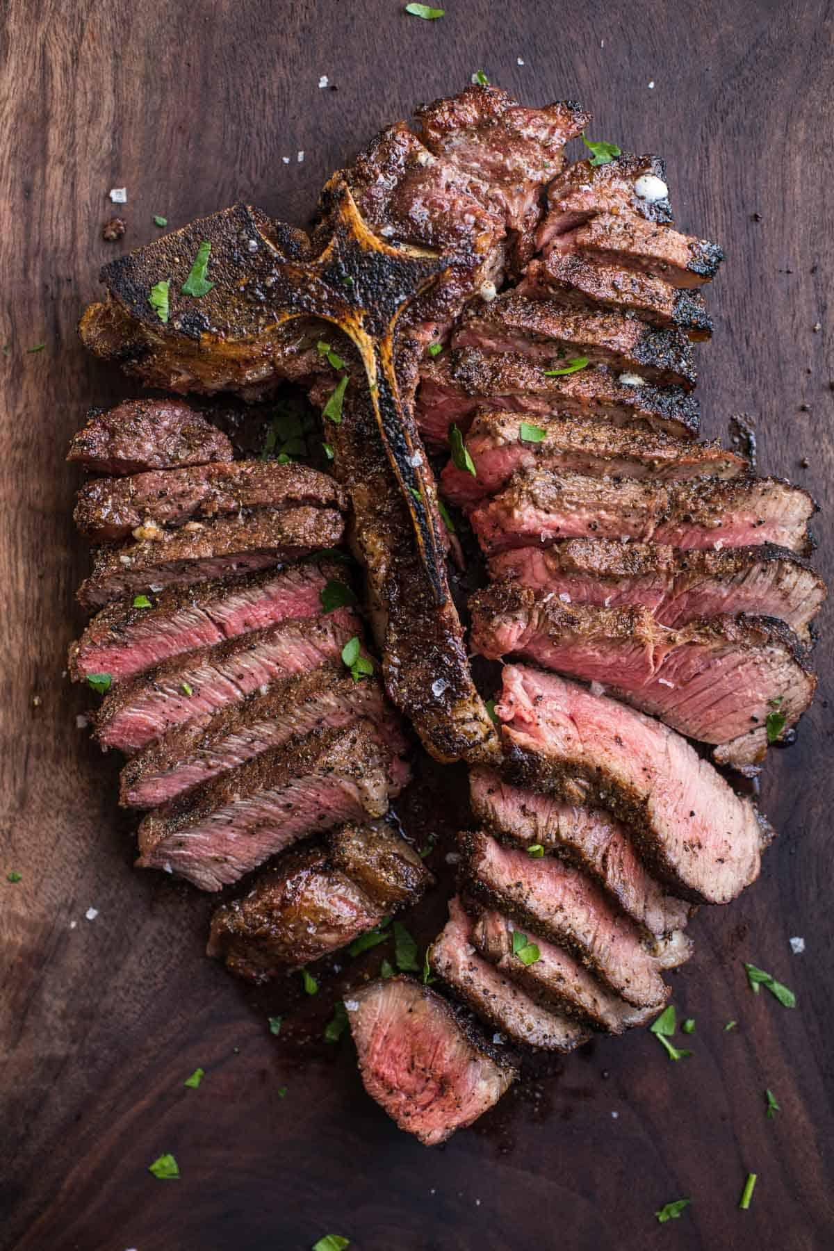 A Grilled Porterhouse Steak, sliced, on a wood cutting board