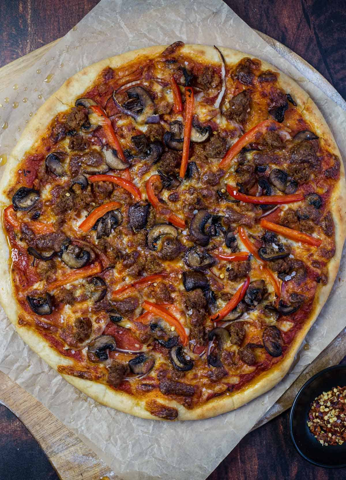 A Pellet Grilled Pizza Topped with Mushrooms, Sausage, and Peppers