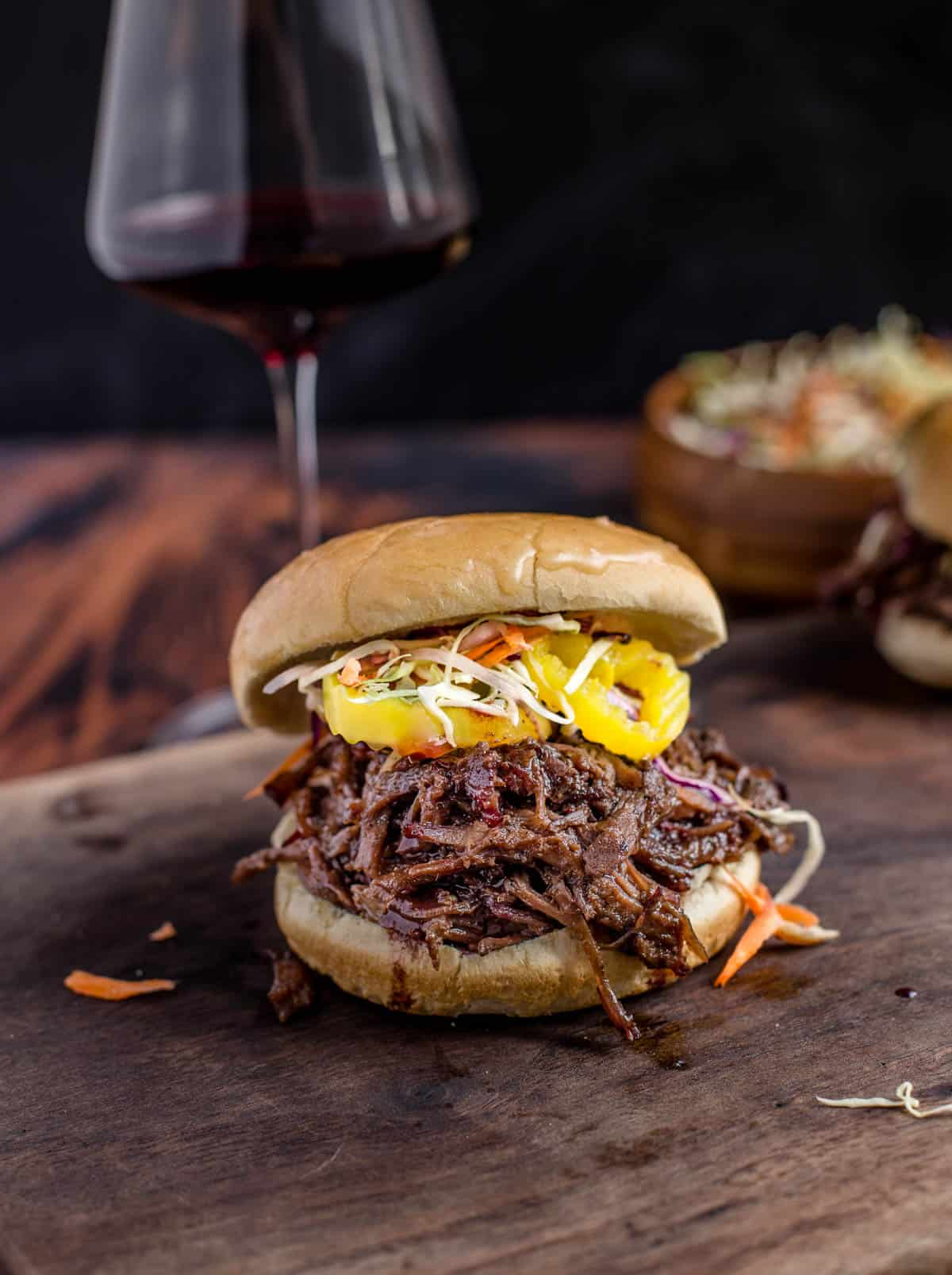 Smoked Pulled Beef Sandwich on a cutting board with a glass of wine