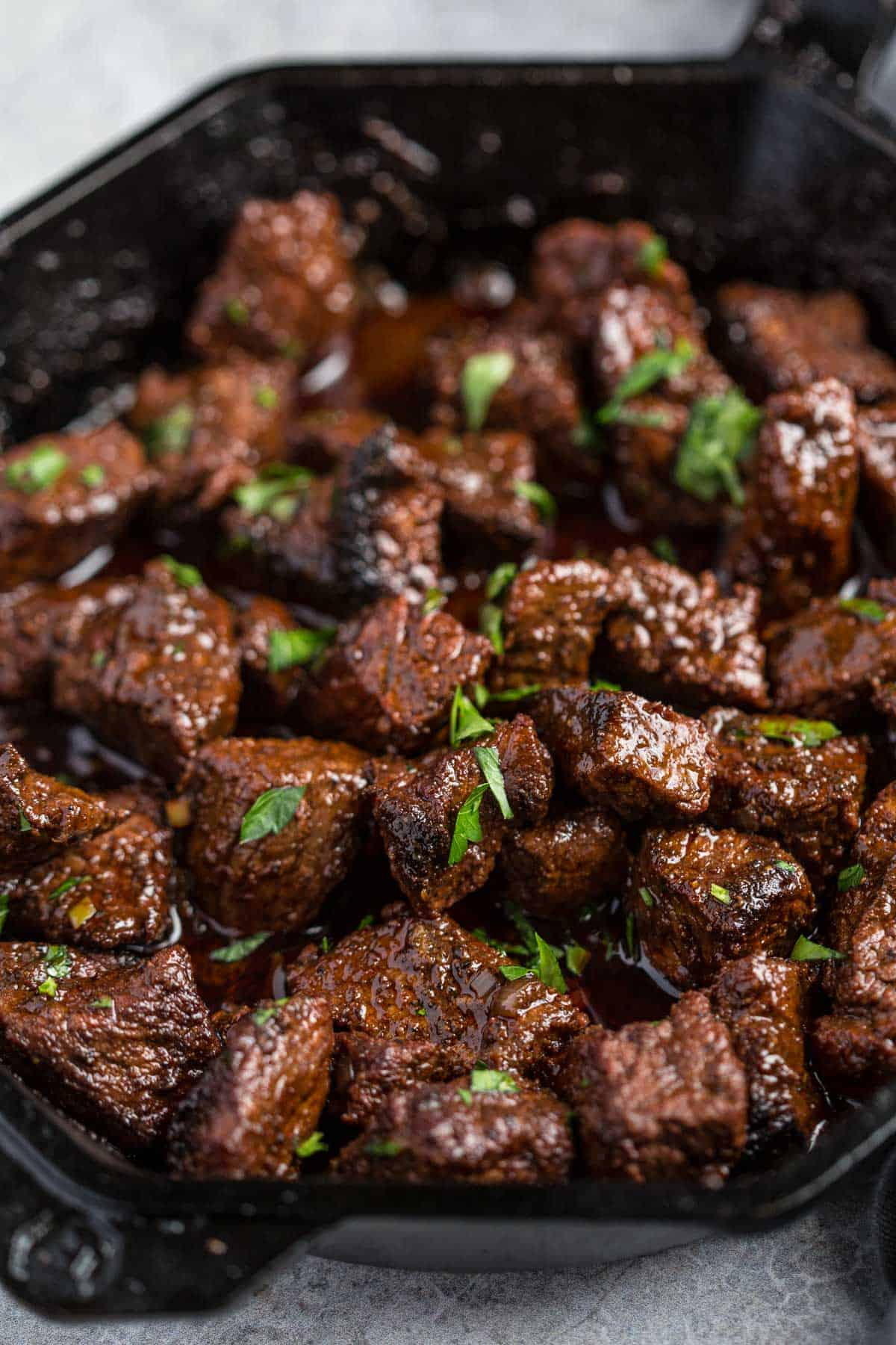 Grilled steak bites in a cast iron pan with a red wine pan sauce