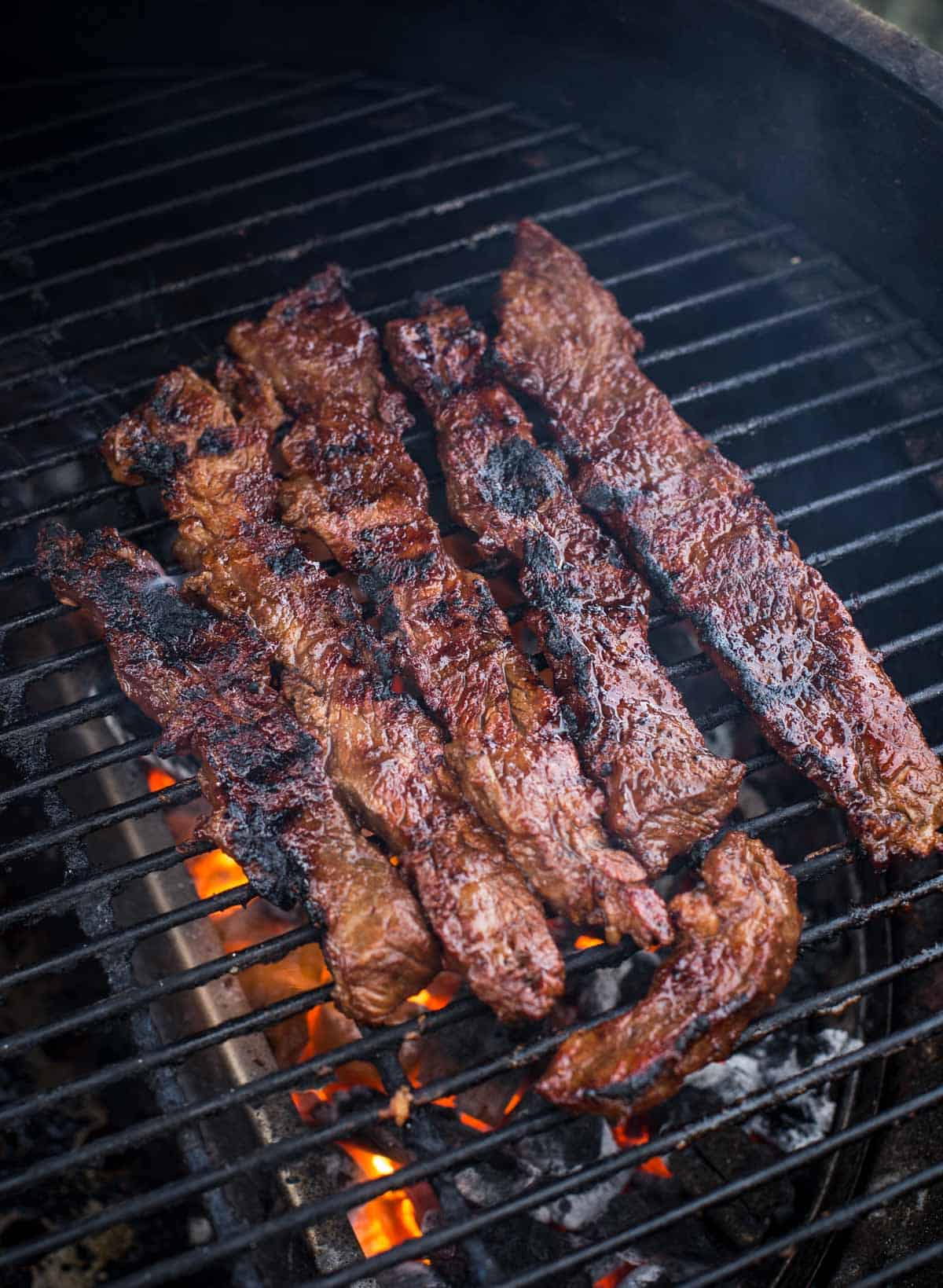 Flanken steak slices cooking on the grill