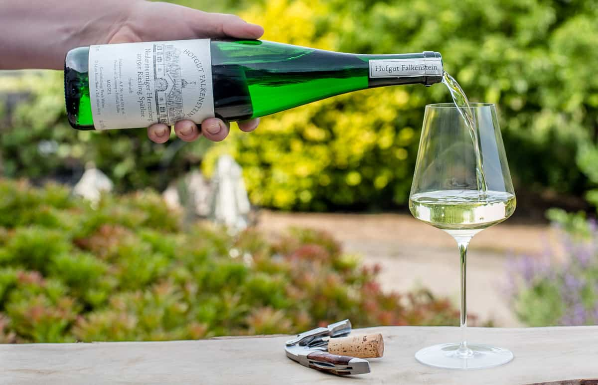 Pouring a bottle of Riesling wine into. wine glass