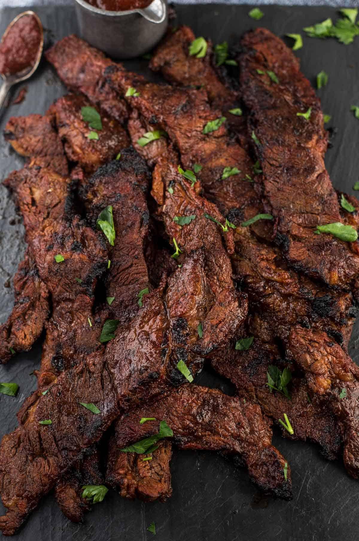 Slices of grilled marinated Flanken steak on a serving platter